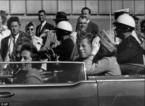 U.S. President John F. Kennedy with his wife Jackie, and Governor of Texas John Connally with his wife Nellie, in the presidential motorcade in Dealey Plaza, Dallas, Texas, before the assassination.